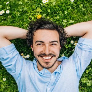 man smiling and laying in the grass
